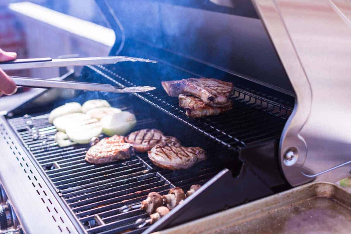 Steak, burgers, onion and mushrooms being seared on a gas grill