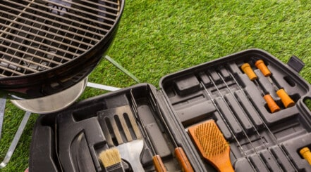 A bbq accessory set next to a kettle grill on grass