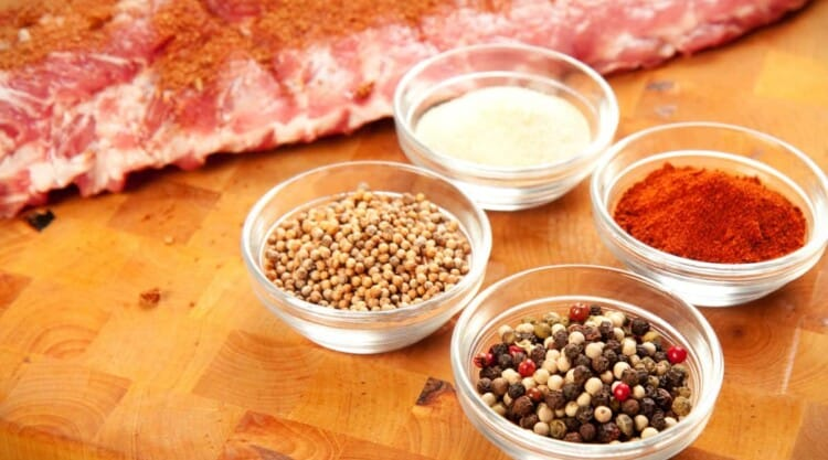 Dry rub ingredients and pork ribs on a wooden cutting board