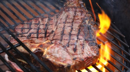 Porterhouse steak being seared on a charcoal grill