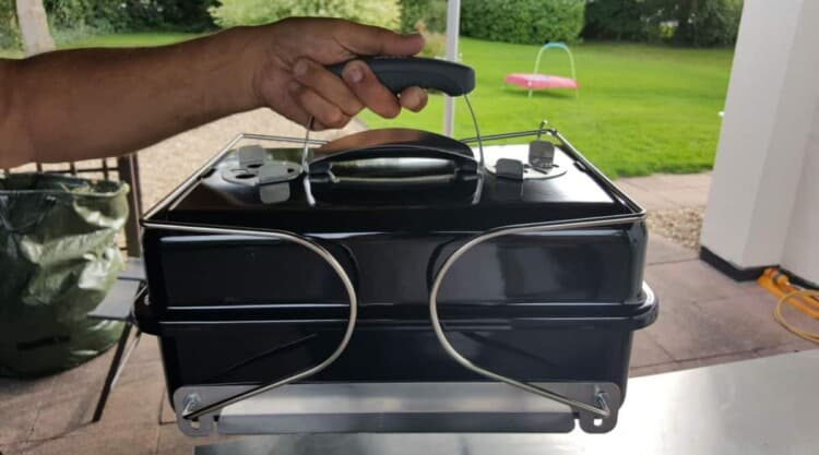 A portable weber go anywhere charcoal grill being carried