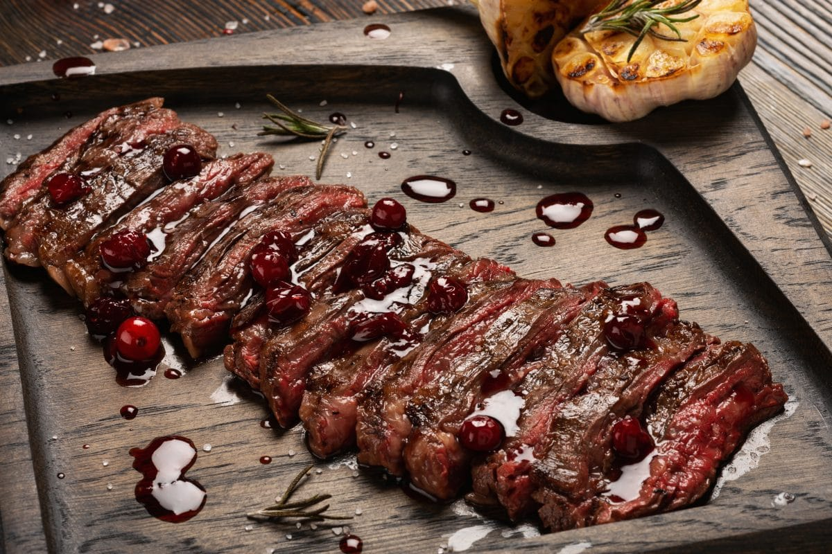 Rare grilled skirt steak, with grilled garlic halves
