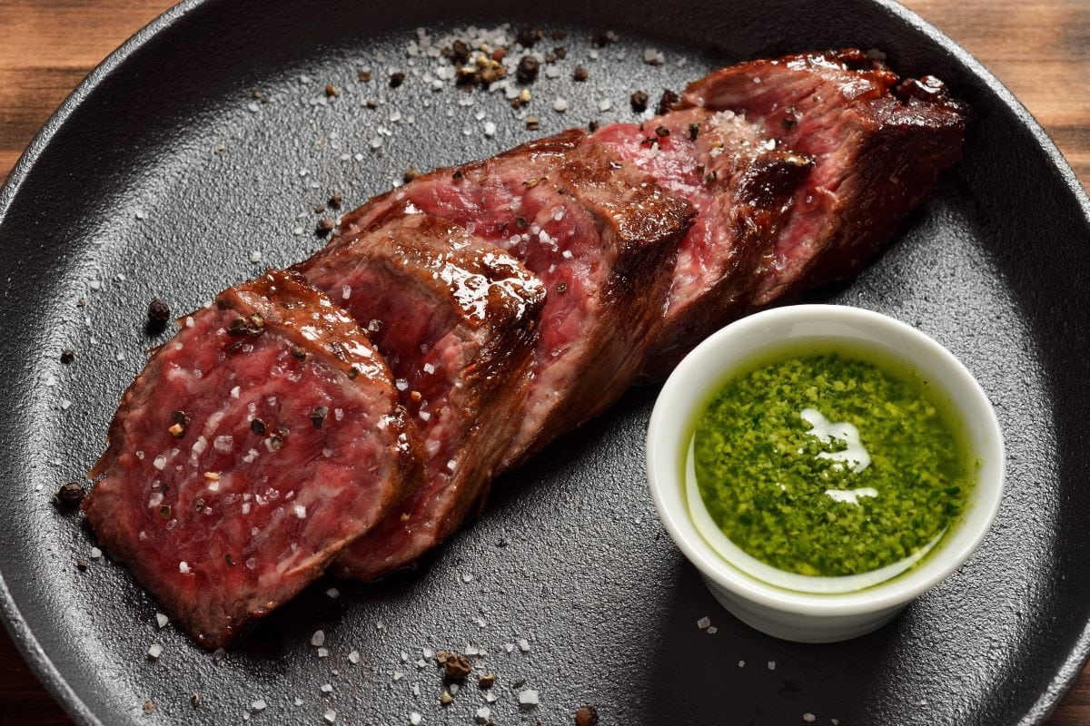 Sliced, grille skit with chimichurri in a white ramekin