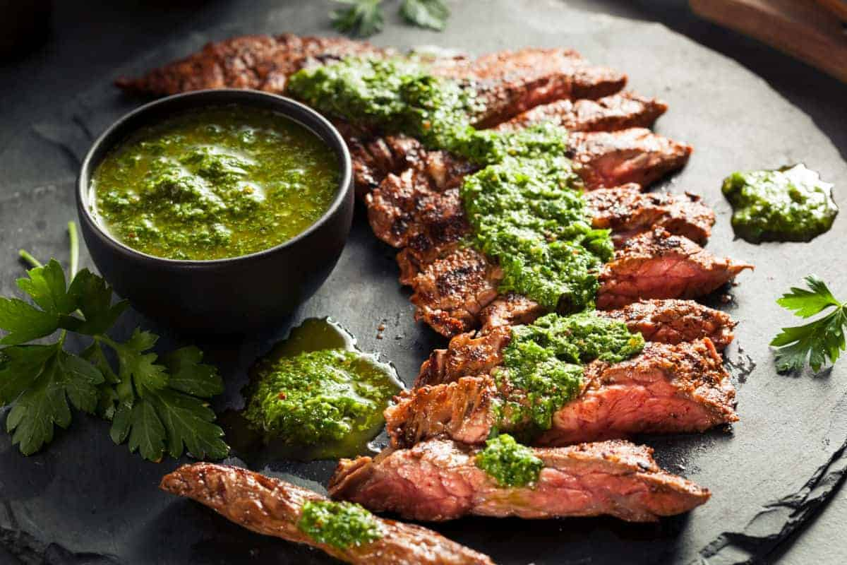 Skirt steak sliced on a cutting board, drizzled with chimichurri