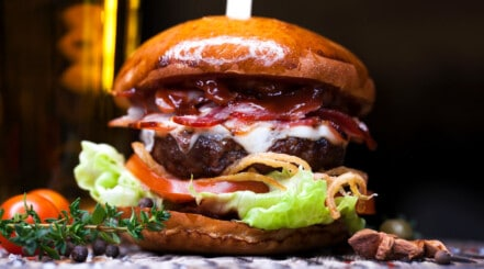 Close up of a burger with tomato and lettuce