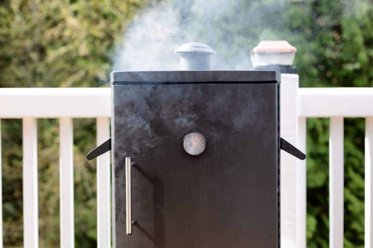 An electric smoker being seasoned, with smoke coming out the top