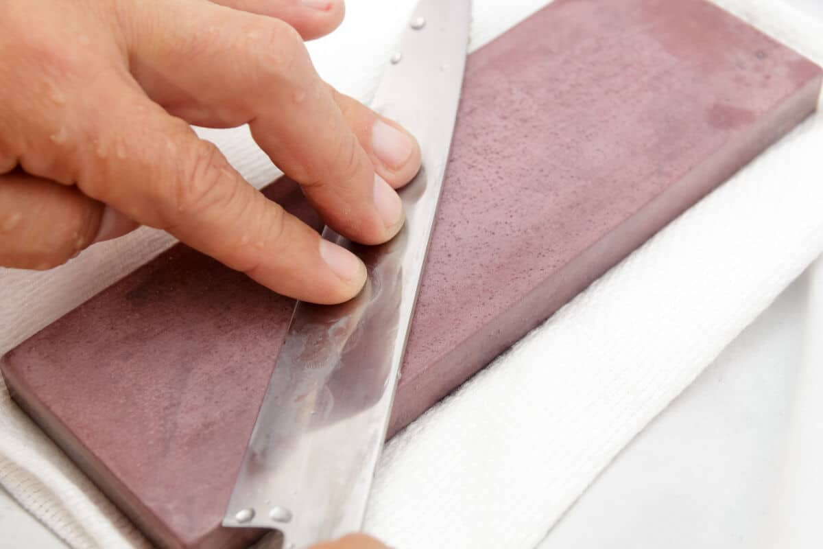 A knife being sharpened on a purple whetstone