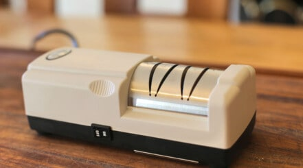 Close up of an i o shen electric knife sharpener on a wooden chopping board