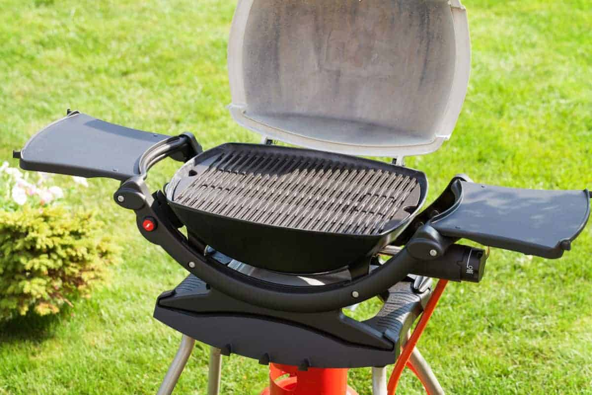 A weber portable gas grill with side tables and lid open on a grass field