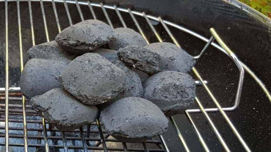 Small pile of charcoal briquettes on a stainless steel grill grate