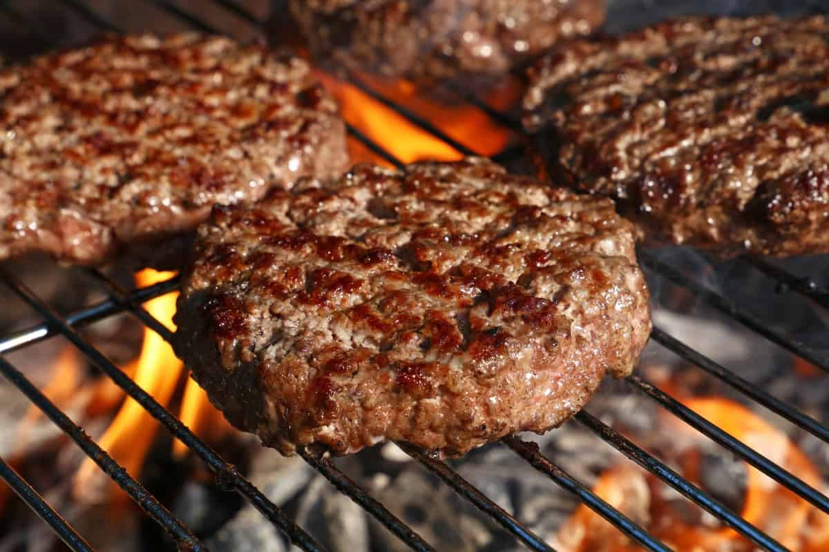 Burgers on a grate over a flaming hot grill