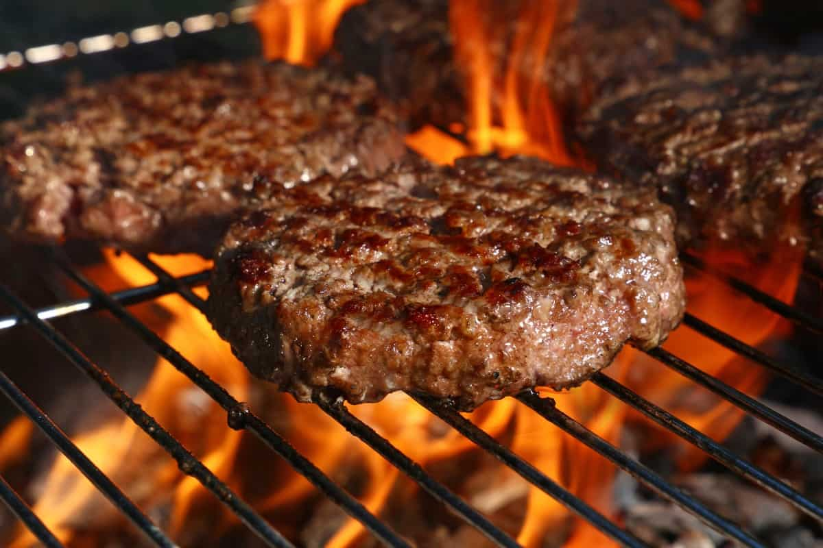 burgers cooking on a hot flaming charcoal grill
