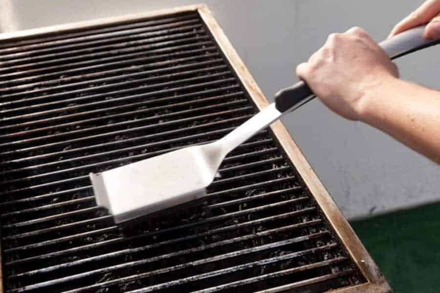 close up of grill grates being scrubbed with a brush