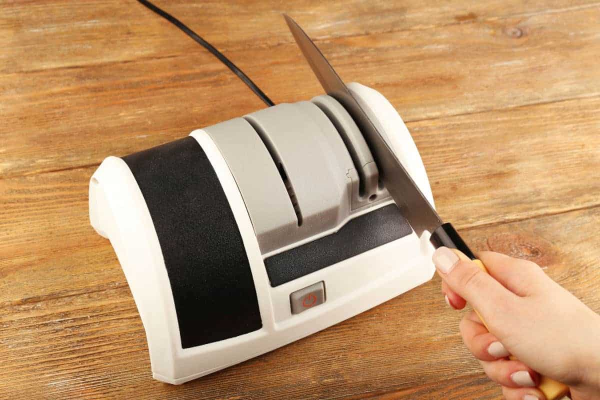A woman's hand drawing a knife through an electric sharpener