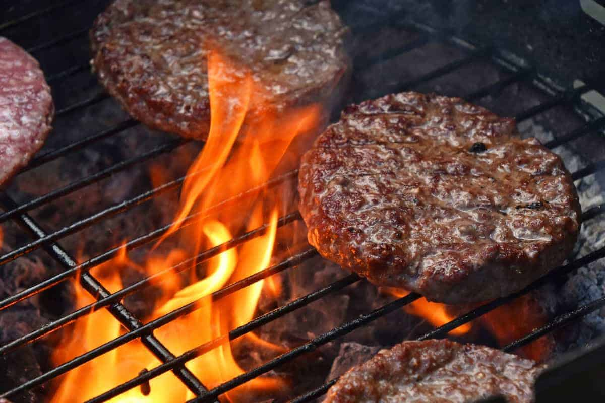 Burgers searing on a grill with flames licking the underside