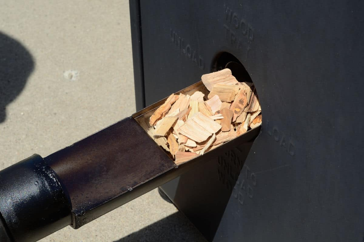 Wood chips being added into an electric smoker via a side opening