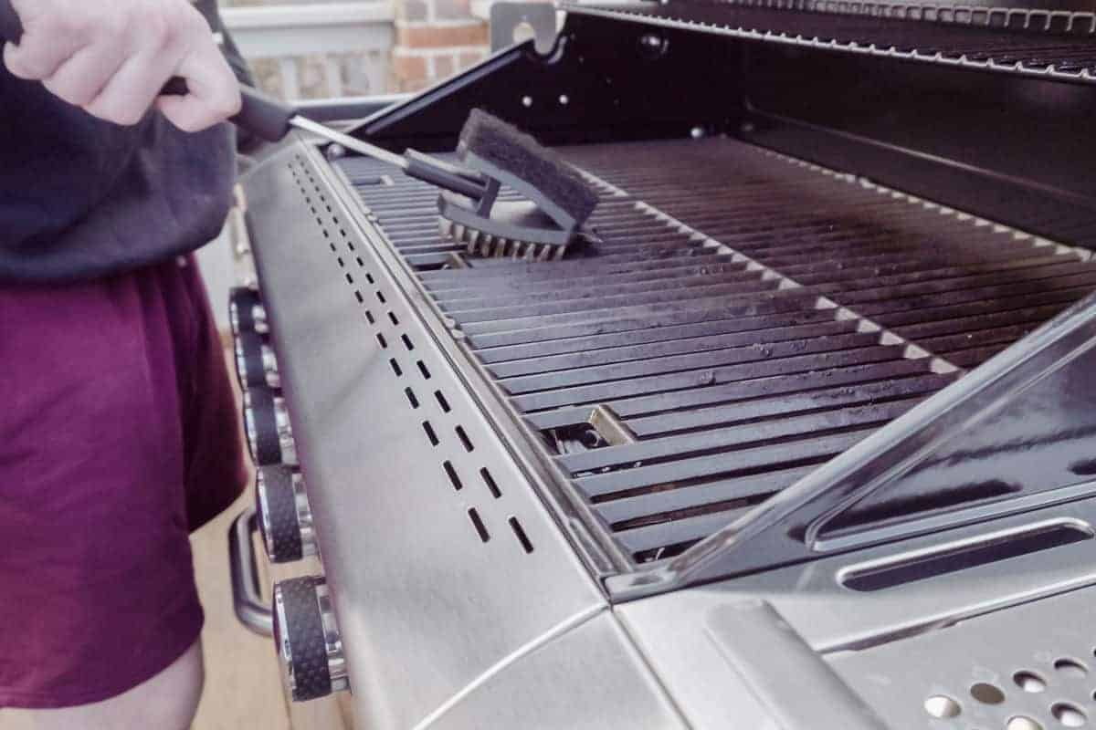A gas grill being cleaned with a reversible grill brush