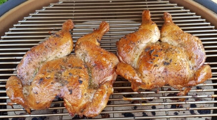Two spatchcock chicken on a kamado grill