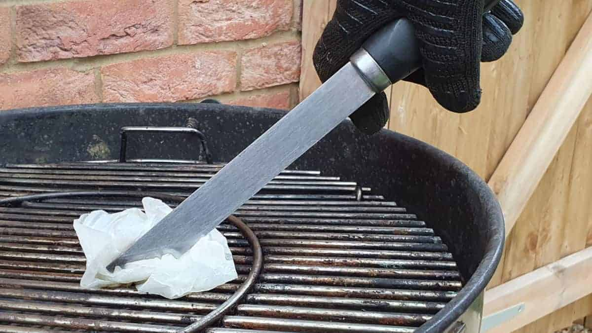 Oiling grill grates with a paper towel and tongs