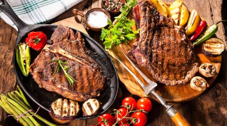 A porterhouse and ribeye steak on a cutting board, with vine tomatoes, greens, and salt
