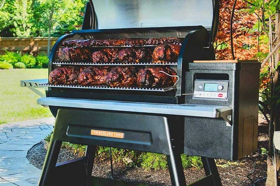 A Traeger timberline 1300 pellet grill loaded with pork butts and lid open