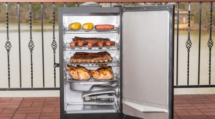 An electric smoker on a wooden balcony, door open and stuffed with food to smoke