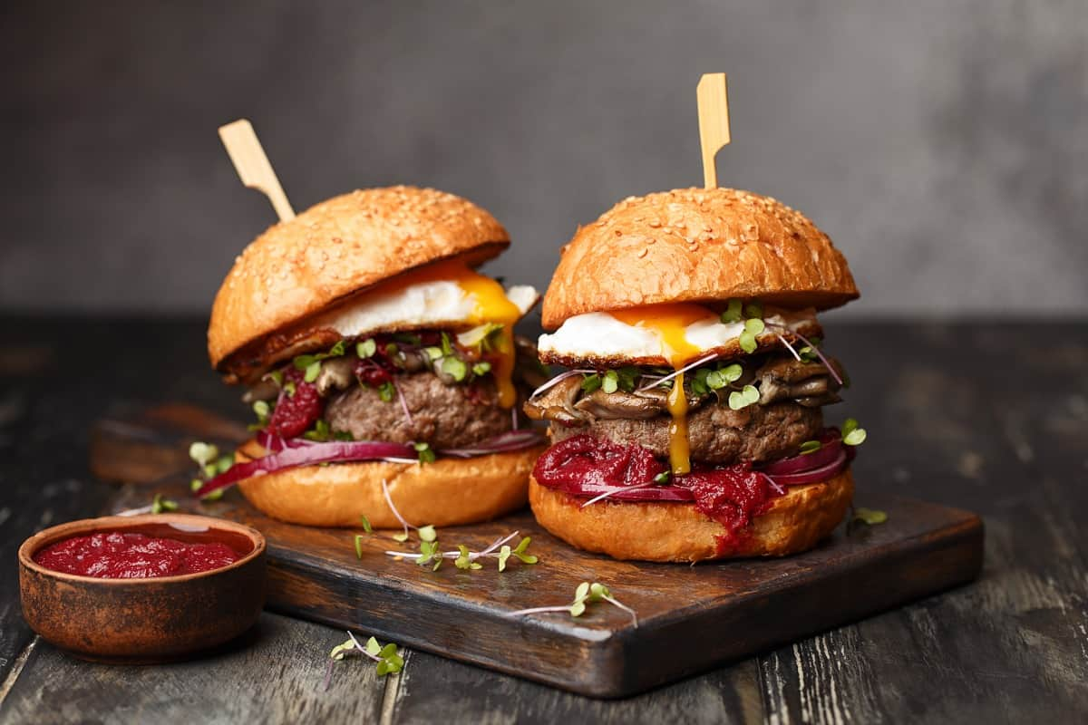 two packed burgers with sticks through them top to bottom, sitting on a wooden cutting board