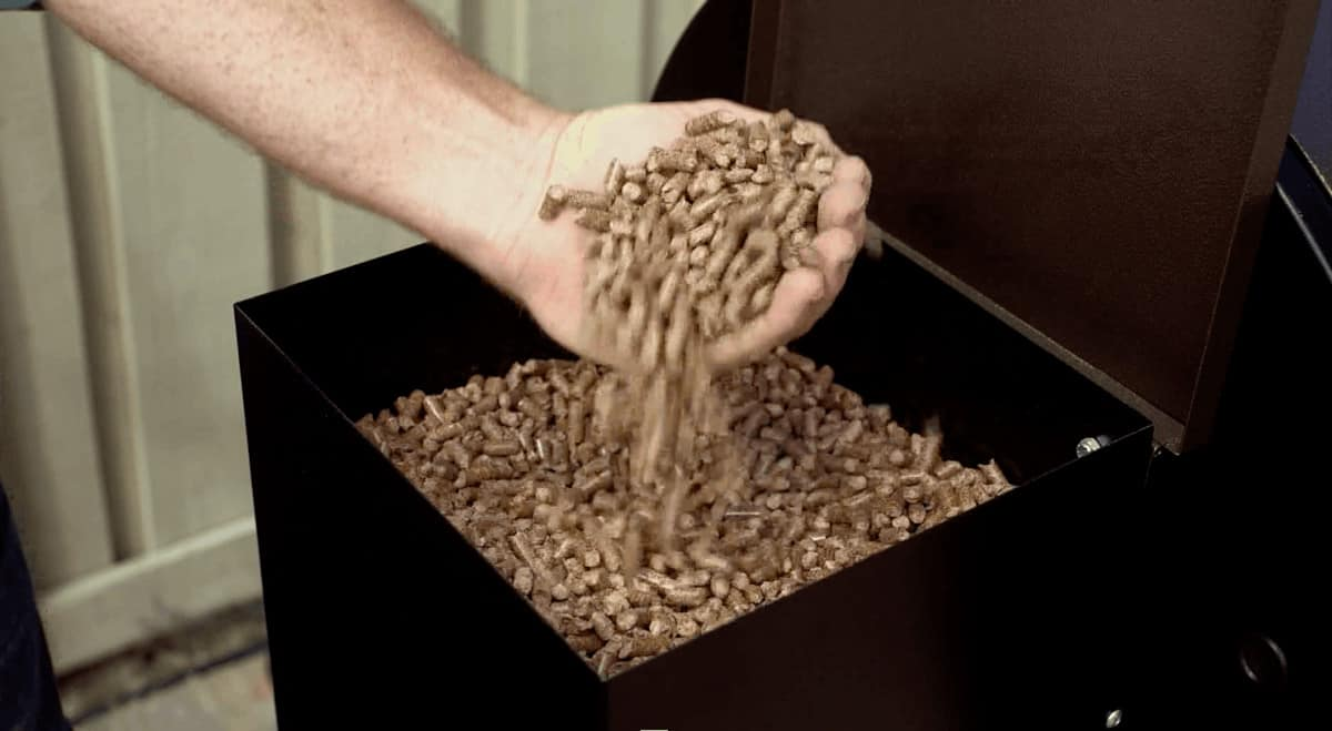 A man with a handful of wood pellets held over a hopper full of them