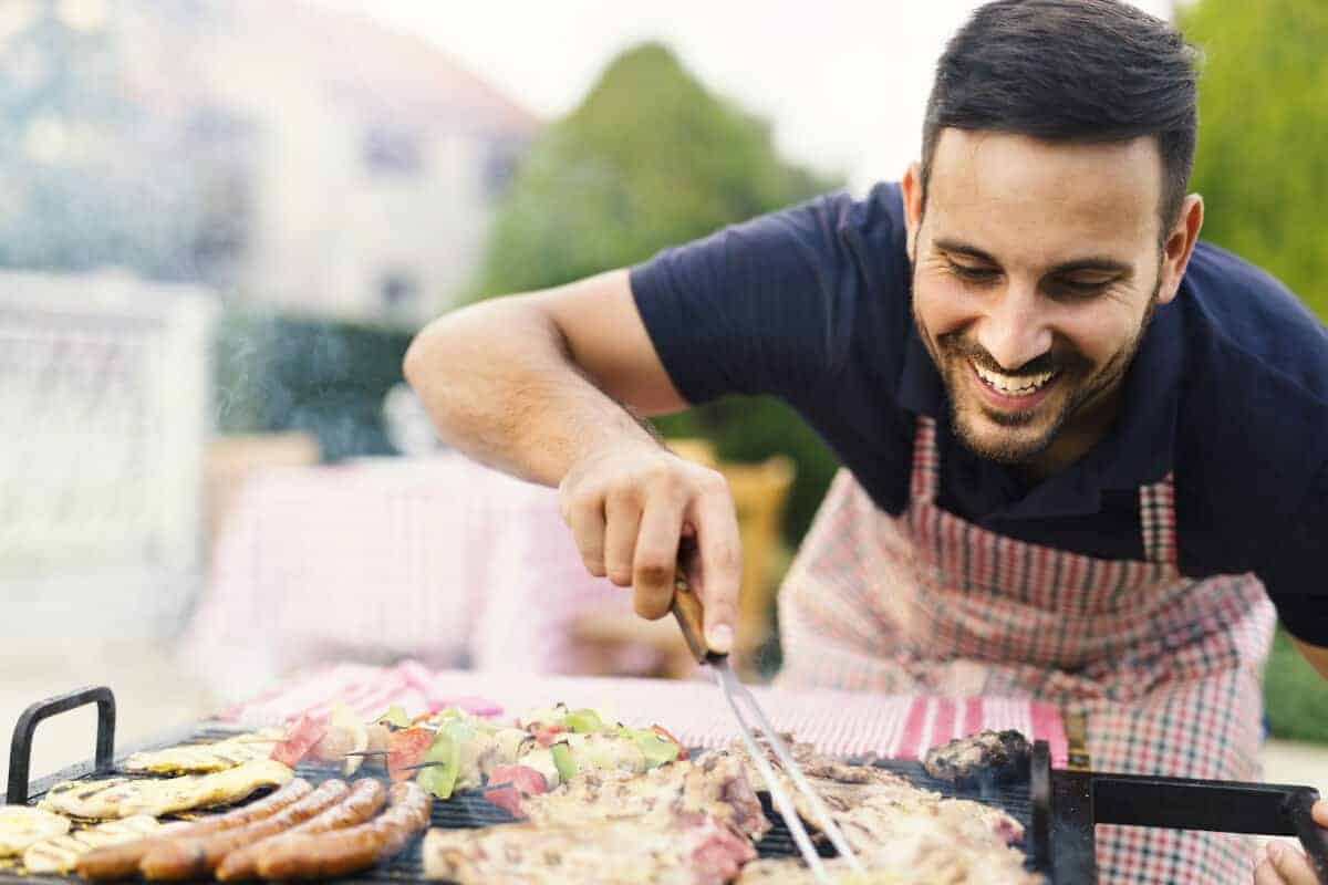 A happy looking man leaning over a BBQ turning meat