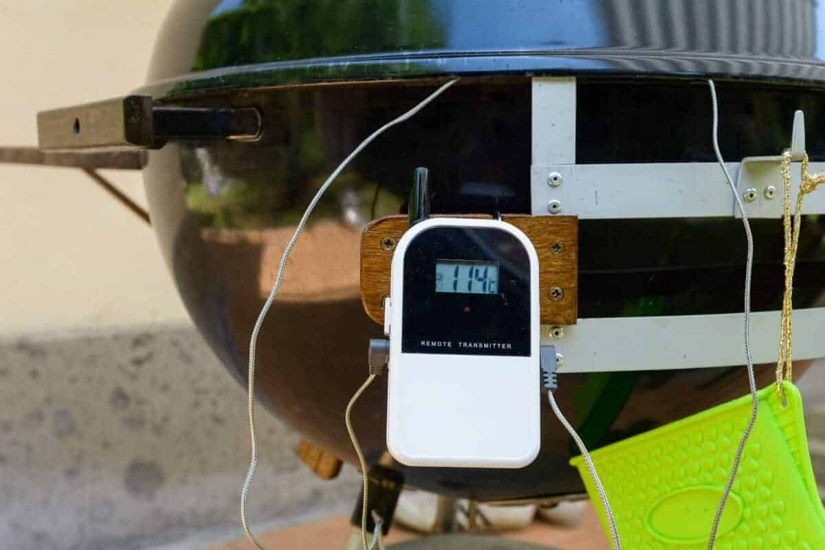 A white dual probe smoker thermometer stuck to the leg of a BBQ