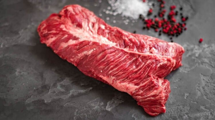 Hanger steak on a slate chopping board with some pink pepper