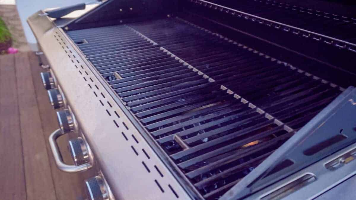 An open gas grill with no food on the grates