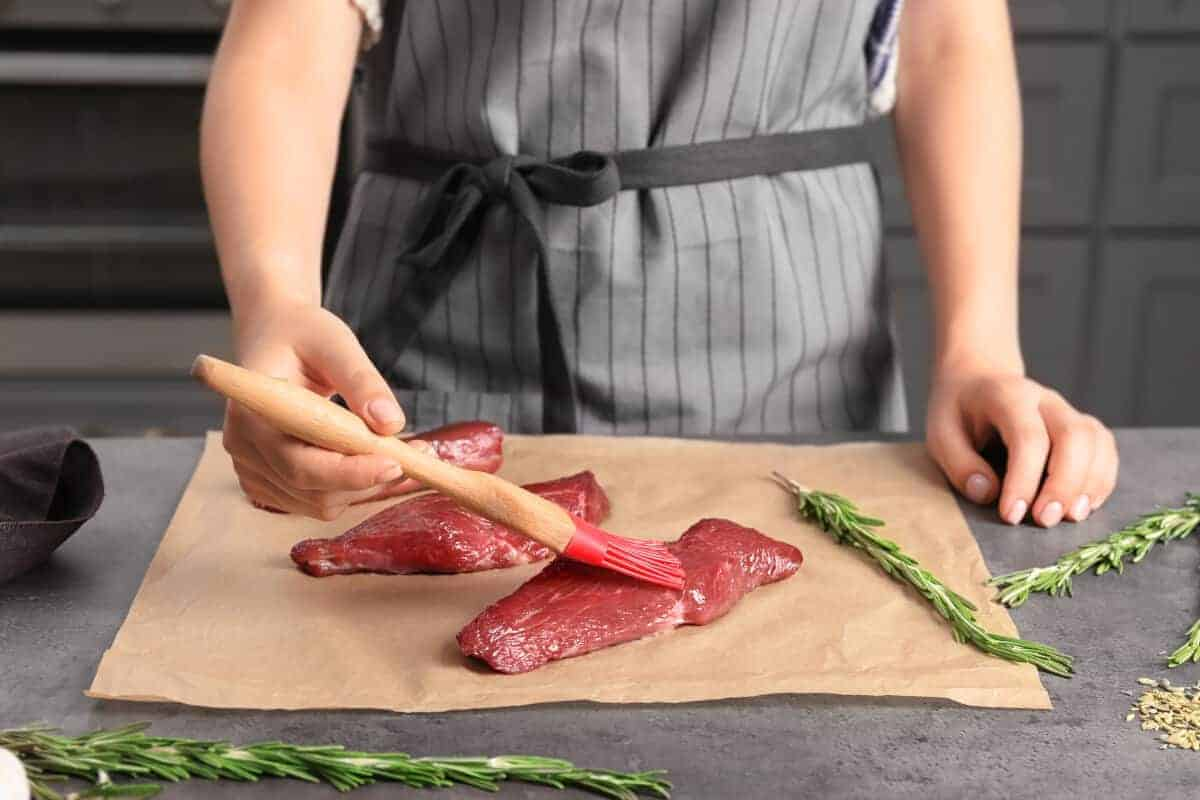 A woman oiling steaks on a chopping board