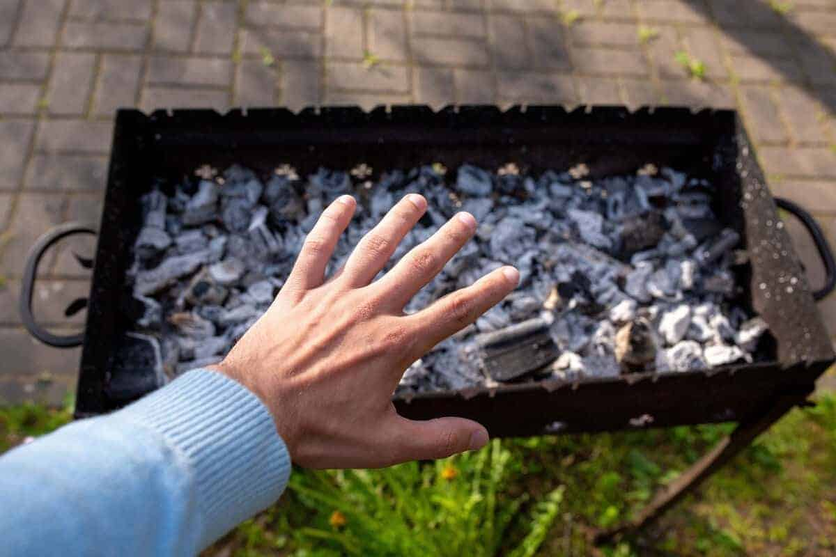 A mans hand held over a hot charcoal grill