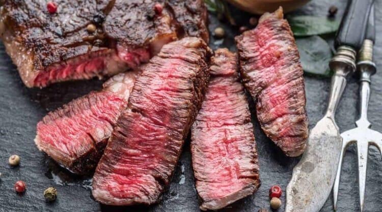 A medium rare grilled ribeye steak next to a sharp artisan knife on a chopping board