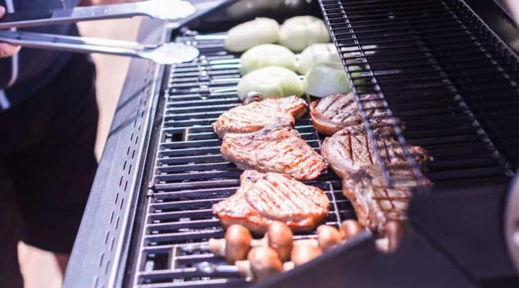 Gas grill with onions, teak and other bits, and a man holding tongs to flip them