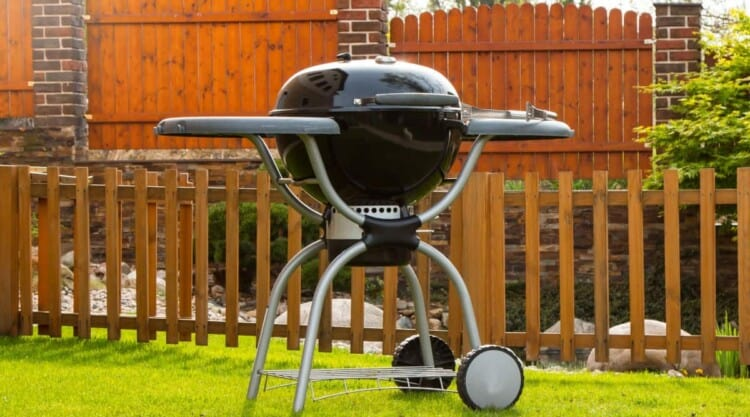 A clean charcoal grill on a grass lawn