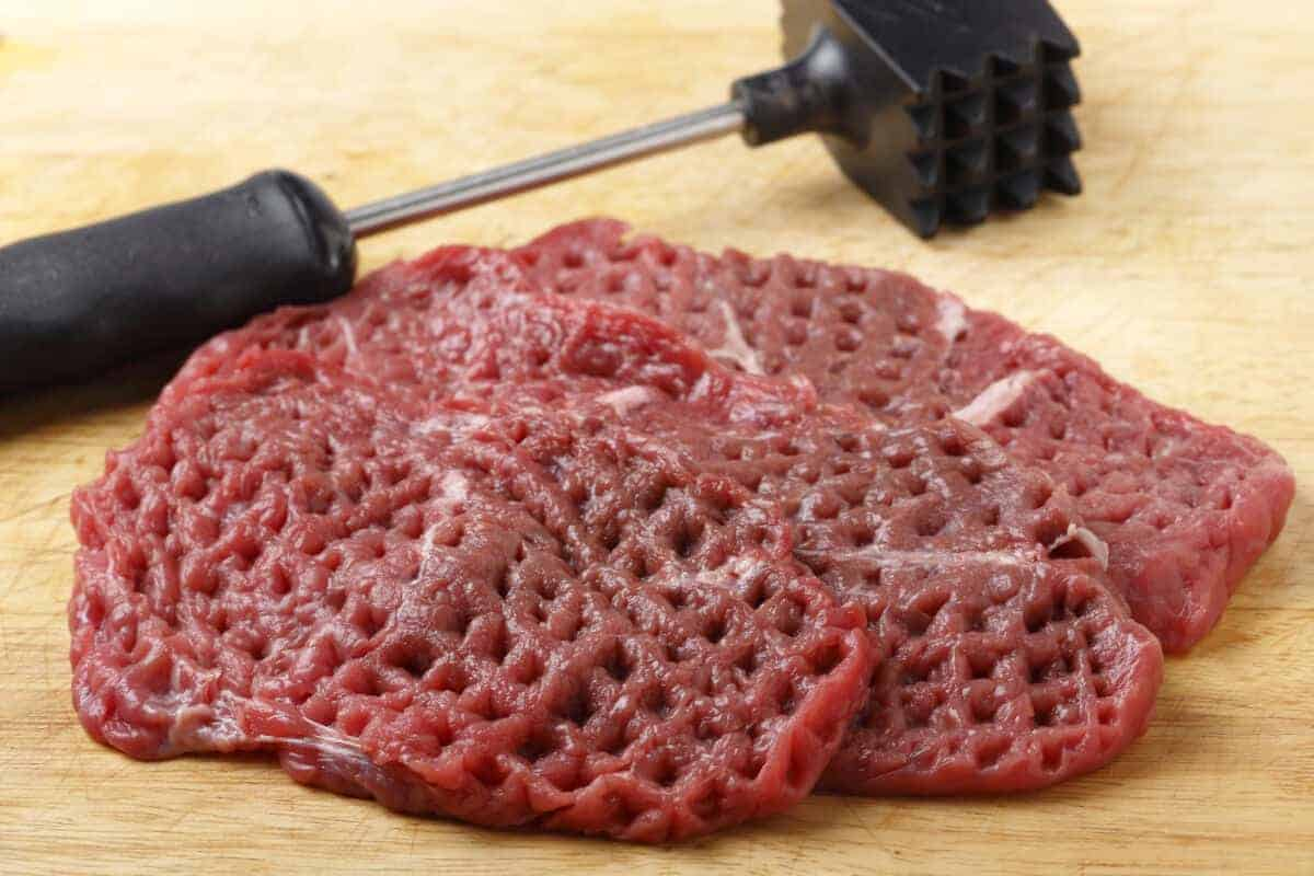 Tenderized steak on a chopping board with a mallet