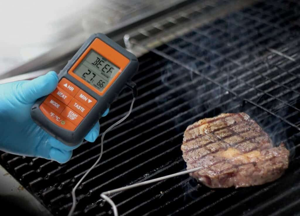 A thermopro smoker thermometer, in a blue gloved hand reading some meat