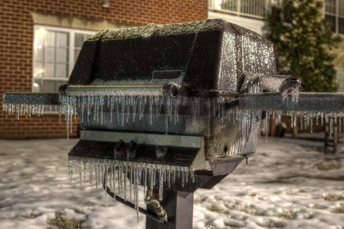 An outside grill covered in icicles in winter