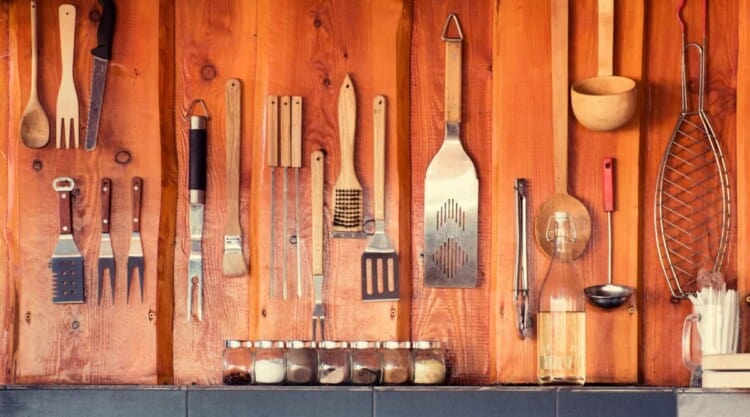 A wide angle shot of a BBQ tools collection hanging from a wooden wall