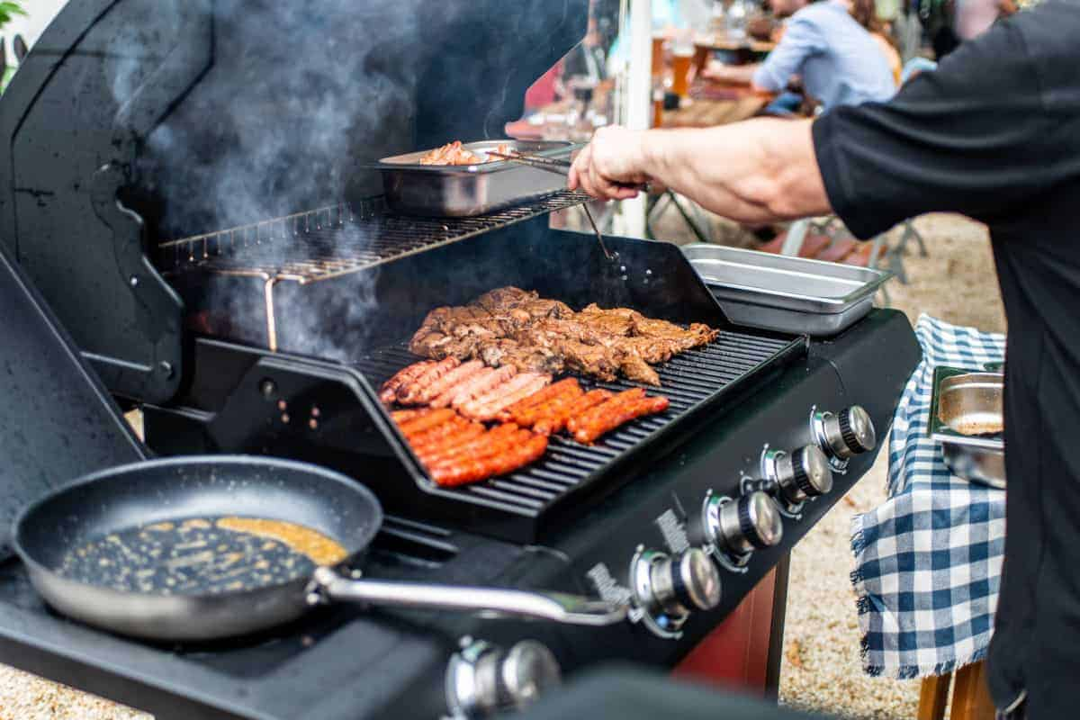 A gas grill with frying pan, bratwurst and steaks cooking