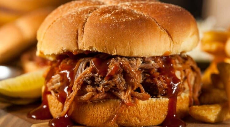 Close up of BBQ pulled pork roll dripping with sauce