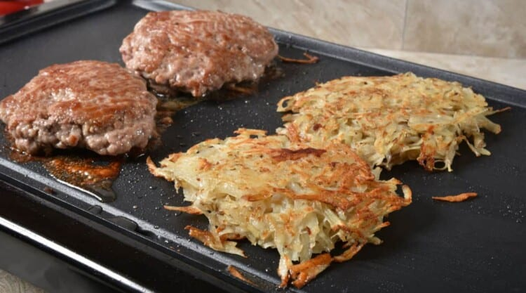 Sausage patties and hash browns on an electric griddle