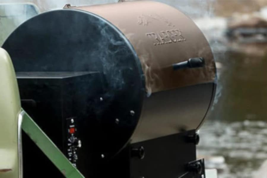 a traeger pellet grill, smoking away on a tailgate