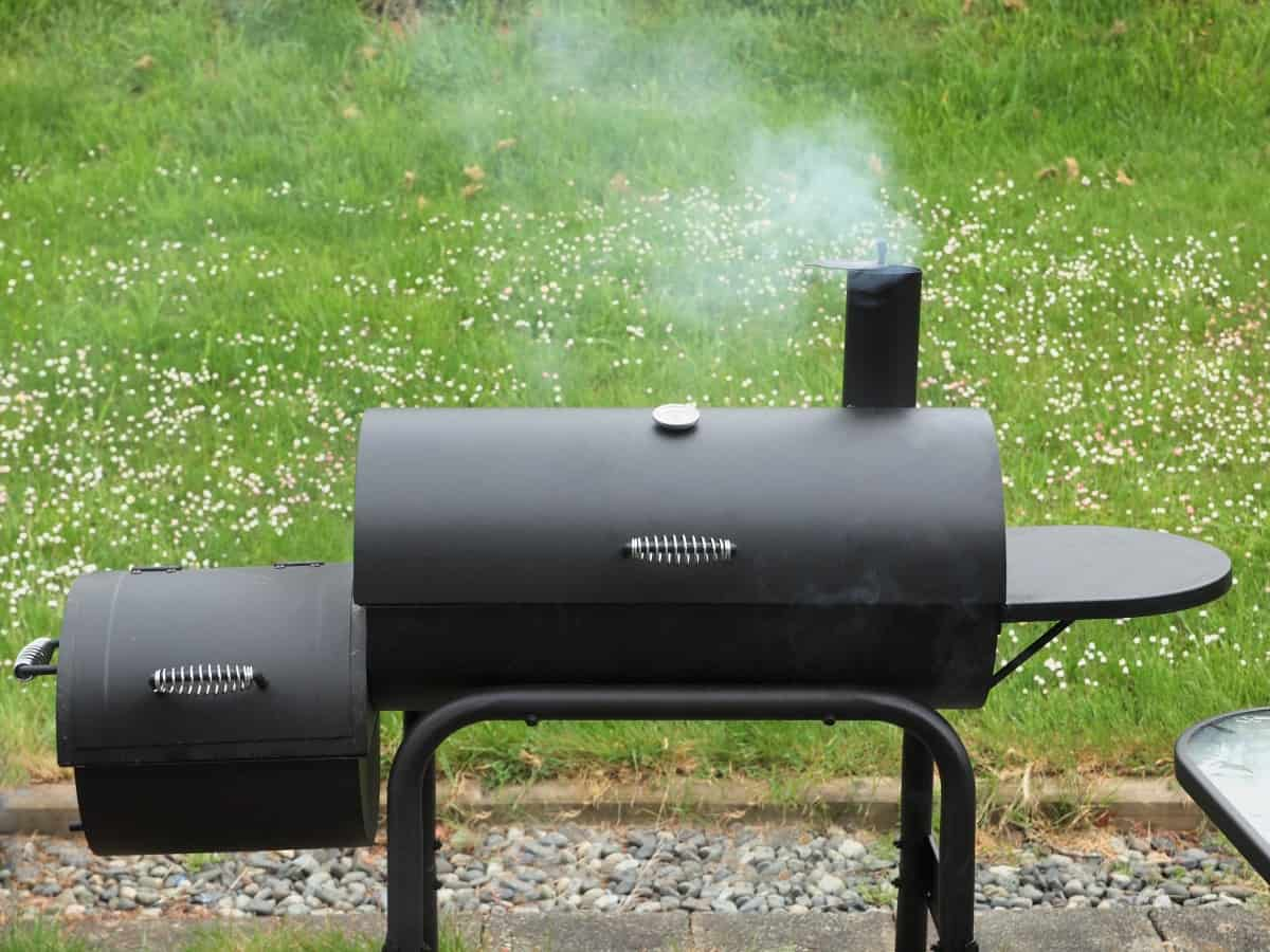 A cheap offset smoker on a patio in front of grass, smoke coming from the chimney