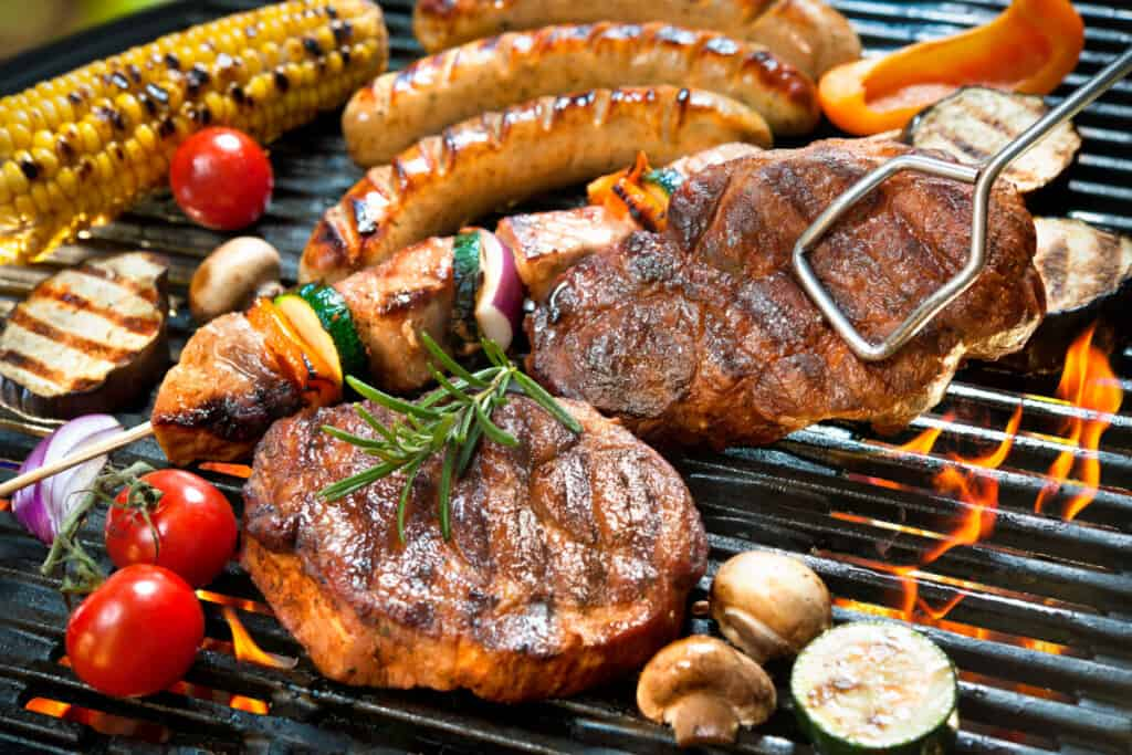 An assortment of meats and vegetables on a hot grill