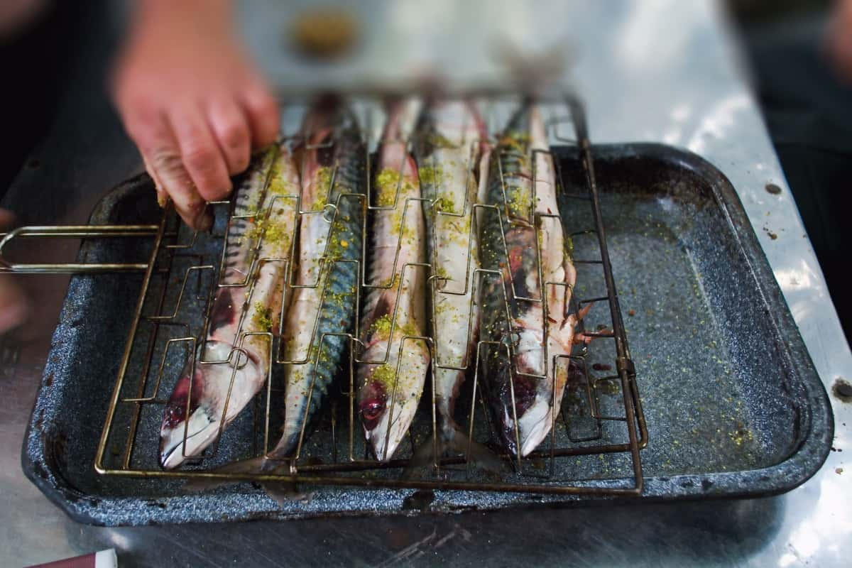 Five whole mackerel being placed into a grill basket