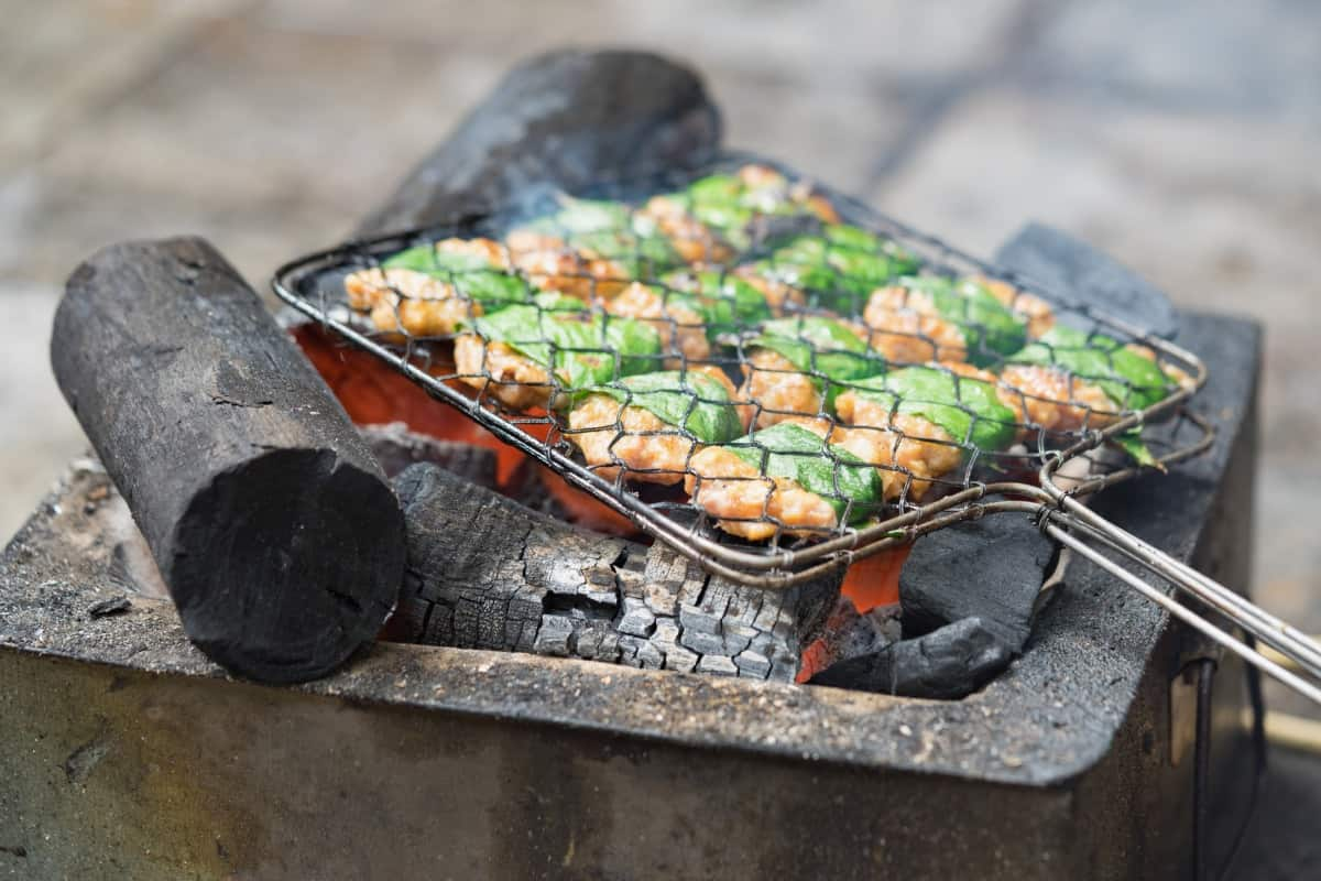 Meat and veg sides in a grill basket over a hot grill
