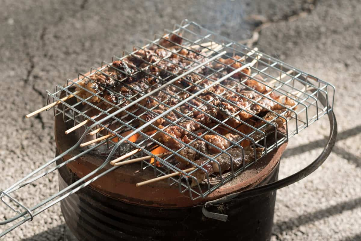 skewers of meat, in a grill basket, over a hot grill